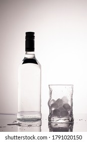 Empty bottle and glass with ice cubes in monochromatic color palette.