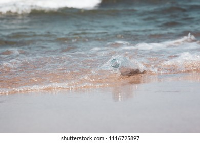 Empty bottle on the beach shore of an ocean, littering plastic waste harming environment concept image