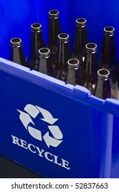 Empty bottles in blue recycle bin