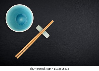 Empty bowl and  bamboo chopsticks on black slate background, top view