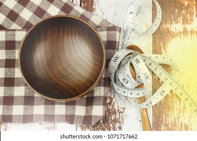 Empty bowl, spoon and measurement tape on the table. Concept of weight management,weight issue,lifestyle changes, weight loss health issue and social issue