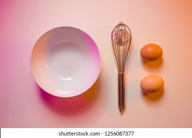 Empty bowl, wire whisk and two eggs - pre cooking preparation in the kitchen. Captured from above (top view). Colorful light - pink and orange tonal transitions.