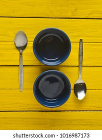 Empty bowls for a julienne and a spoon on a yellow rustic wooden table. Top view.