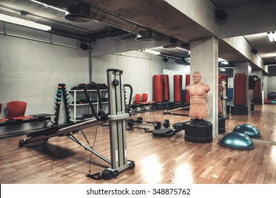 Empty boxing area in the gym. Fitness club with equipment. Sports background with rough concrete walls