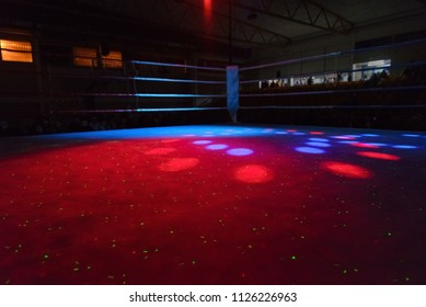 empty boxing ring in the beams of searchlights