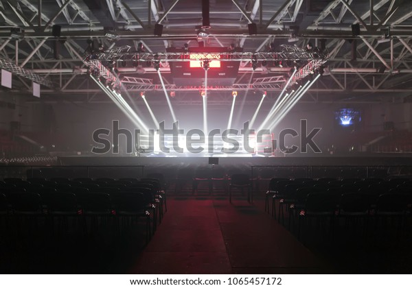 Empty boxing ring in the light of searchlights, around it the empty seats of the auditorium.