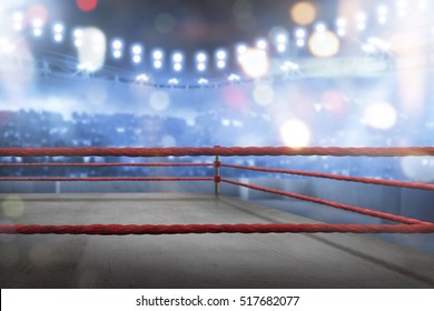 Empty boxing ring with red ropes for match in the stadium arena