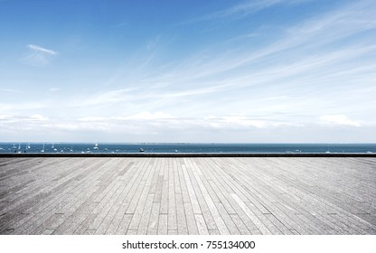 empty brick floor and blue sea in blue cloud sky