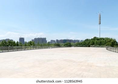 empty brick floor and cityscape against a sunny sky