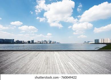empty brick floor and cityscape of hangzhou in blue cloud sky