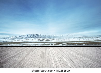 empty brick floor and snow mountains in blue cloud sky