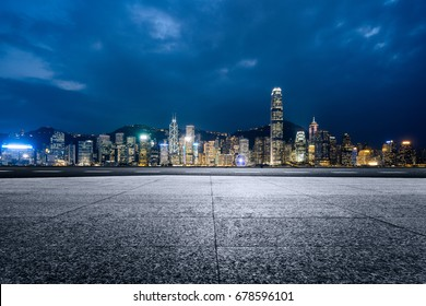 empty brick platform with Hong Kong skyline in background at night.