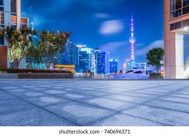 empty brick platform with Shanghai skyline in background at night.