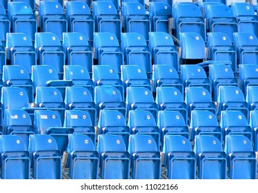 Empty bright blue stadium seats create repeating pattern. Horizontal image is filled with folded seats with one seat being unfolded, in the upper right. Six rows of eight chairs each.