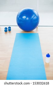 Empty bright sports hall with dumbbells and sport ball on background