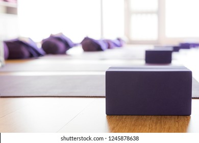 Empty, bright Yoga studio with mats and foam blocks. Wooden floor.