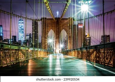 Empty Brooklyn Bridge pedestrian walkway before sunrise.