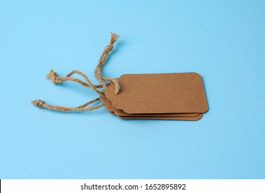 Empty brown paper tags tied with white string. Price tag, gift tag, sale tag  on the blue background, close up