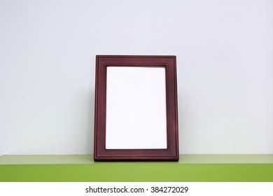 Empty Brown Picture Frame on Green Table