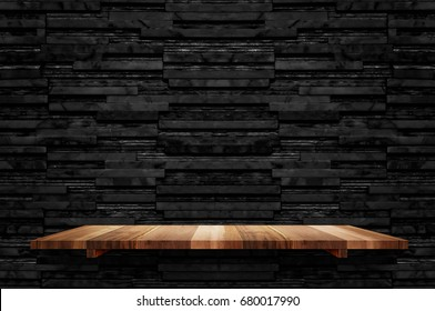 Empty brown plank wood shelf at black layer marble tile wall background,Mock up for display or montage of product or design