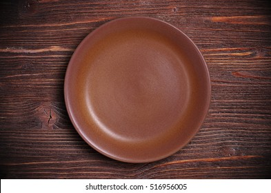Empty brown plate on dark wooden background, top view