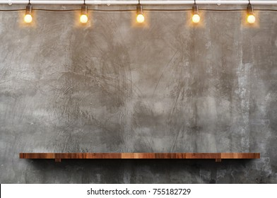 Empty brown wood plank board shelf at grunge concrete wall with light bulb string party background,Mock up for display or montage of product or design.