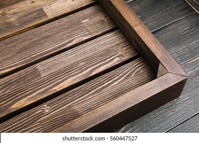 Empty brown wood serving tray on the black wooden table, copy space