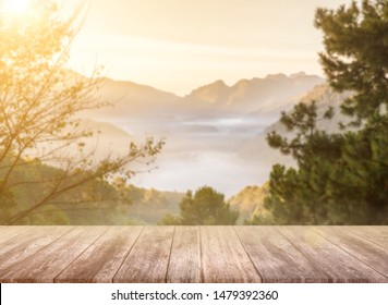 Empty brown wood table top in front of art abstract blur landscape of mountain and sun light in the background and yellow pipe forest for your display or montage