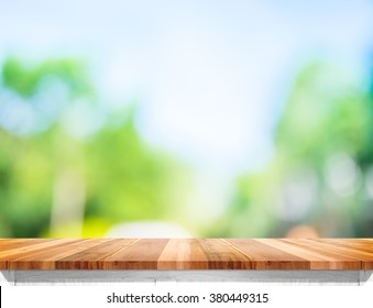 Empty brown wood table top with sun and blur green tree bokeh background, Template mock up for montage of product