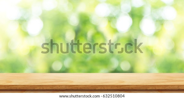 Empty brown wood table top with green blur nature background and sun light,Mock up for display or montage of product,panoramic view,banner size for advertise on online media