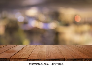 Empty brown wooden table and blur background of resturant lights ,can be used for montage or display your products with copy space ,business concept