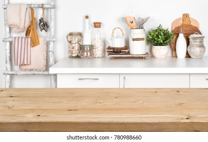 Empty brown wooden table with blurred image of kitchen interior