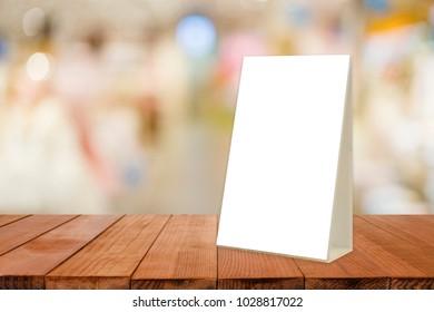 Empty brown wooden table and Coffee shop interior with Mock up Menu frame in Bar restaurant ,Stand for booklets with white sheets of paper acrylic tent card on cafeteria blurred background