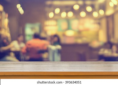 Empty brown wooden table and Coffee shop interior with some people meeting blur background with bokeh image can be used for montage or display your products