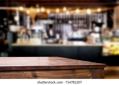 Empty brown wooden table and Coffee shop or restaurant blur background with bokeh image. for your photomontage or product display