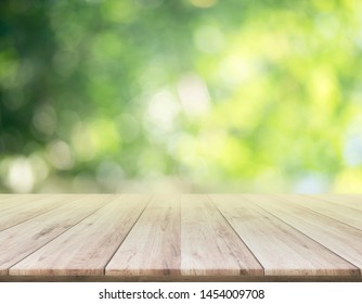 Empty brown wooden table in front of art abstract bokeh background with shiny of sunlight for your display or montage