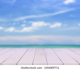 Empty brown wooden table in front of art abstract bokeh background of seascape and blue sky in summer for your display or montage