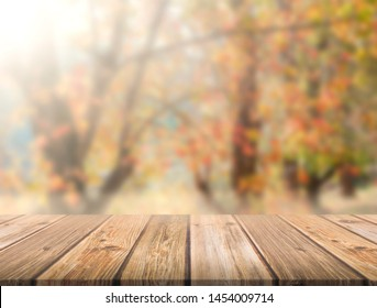 Empty brown wooden table in front of art abstract bokeh background of maple trees in autumn with shiny of sunlight for your display or montage