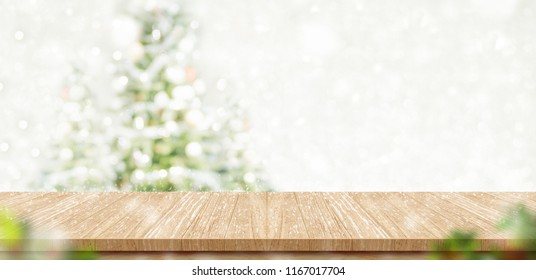 Empty brown wooden table top with abstract muted blur christmas tree and snow fall background with bokeh light,Holiday backdrop,Mock up banner for display or montage of product