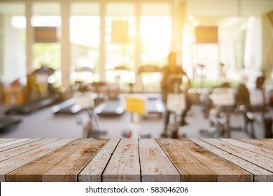 Empty brown wooden table top on blurred background of fitness gym,Young People group of women and men doing sport,interior of new modern club with equipment ,copy space