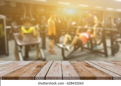 Empty brown wooden table top on blurred background of fitness gym,Young People group of women and men doing sport,interior of new modern club with equipment
