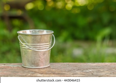 empty bucket on the board on a background of green.