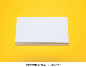Empty business cards on yellow background - closeup shot