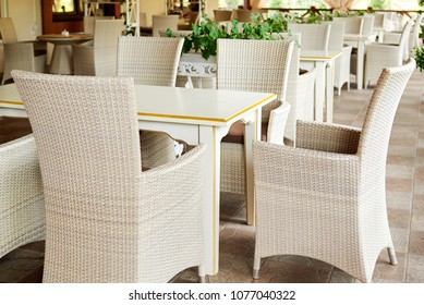 Empty cafe with rattan wicker armchairs and tables on summer garden terrace outdoor, free space. Table and chairs in empty cafe. Wicker furniture rattan chairs on terrace