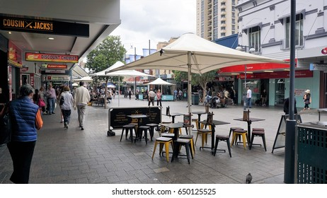 Empty cafe or restaurant with chairs, tables and umbrellas on a busy Sydney street in Bondi on 5 Feb 2016. In view are people walking, shops, sign boards, buildings, windows, billboards, street lights