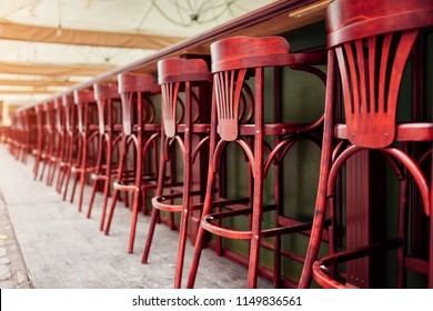 Empty cafe. Wooden chairs beside bar counter. Red vintage seats in row