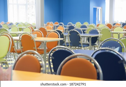 An empty cafeteria interior with blue, green, orange chairs