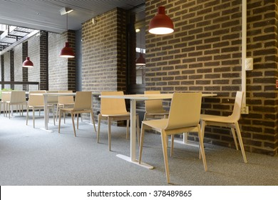 An empty cafeteria interior shot. Large windows letting in light.