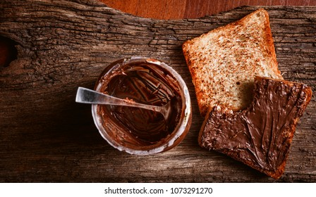 Empty can of chocolate paste with a spoon inside and bitten toast bread with chocolate paste spread on it