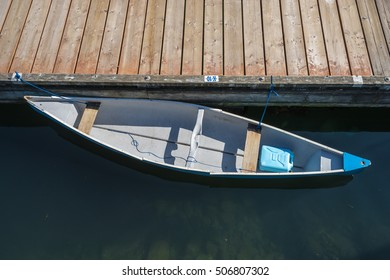 Empty canoe on calm water tied up to a wooden dock